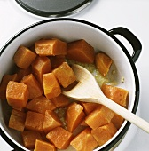 Browning pieces of pumpkin in a pan