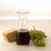Carafe of red wine, parmesan and green grapes beside of