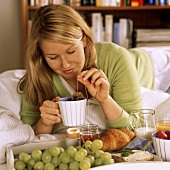 Young woman with breakfast tray and tea cup on bed