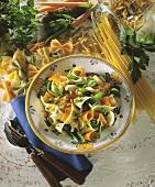Ribbon noodles with carrot strips, mangetouts & basil