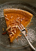 A piece of pumpkin pie with slivered almonds