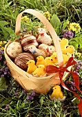 Chip basket in meadow with Easter baking, chocolate Easter eggs
