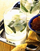 A glass of Caipirinha on tray with nachos and dip