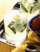 Ein Glas Caipirinha auf Tablett mit Nachos & Dip