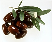 A heap of black olives and an olive branch