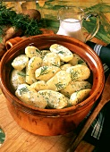 Potatoes in clay pot with dill cream sauce
