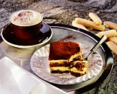 Piece of tiramisu on plate, cappuccino & sponge finger on side