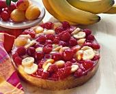 Fruit cake with berries, bananas, peaches and cherries