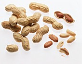 Several opened and unopened peanuts in heap