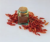 Chili powder in jar, dried chili peppers beside it