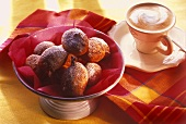 Fritters in bowl, cup of cappuccino behind