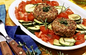 Frikadeller on tomatoes and courgettes