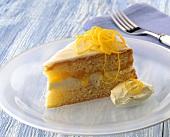A piece of orange cake with orange cream & orange zest