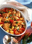 Spanish chicken in roasting dish with peppers & tomatoes