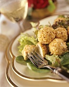 Goat's cheese balls with nut crust on salad leaves