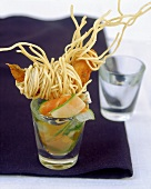 Fried shrimps with udon noodles and vegetables in a glass