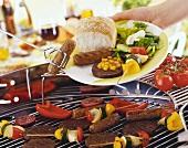 Gegrilltes Würstchen wird mit Grillzange auf Teller gelegt