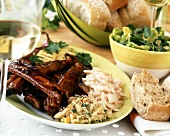 Spare ribs on plate with salads and white bread