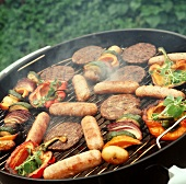 Vegetables, meatballs and sausages on grill