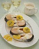 Poached salmon cutlets with oranges and cream sauce