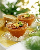 Gazpacho in bowls with olive rings & grated cheese
