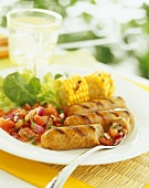 Grilled sausages, sweetcorn and lettuce