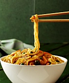 Chop suey in bowl and chopsticks