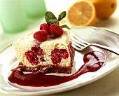 A piece of raspberry quark cake with raspberry sauce on plate