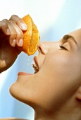 A Woman Squeezing Juice From an Orange into her Mouth