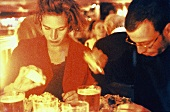Man and Woman in Restaurant; Salting Food