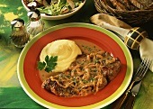 Steak with onions with mashed potato on plate