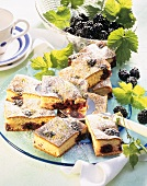 Semolina slices with blackberries on cake plate