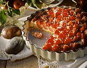 Plum and coconut tart in a china dish, decoration: plums