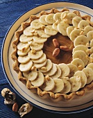 Short pastry banana tart with peanuts on plate