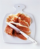 Three slices of ham on chopping board with knife