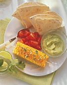 Grilled corncobs with avocado dip and tortillas
