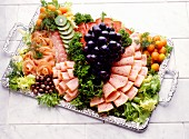 Cold cut platter garnished with salad and fruit