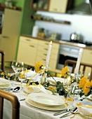 Mit gelben Blumen und Efeu dekorierter Tisch in der Küche