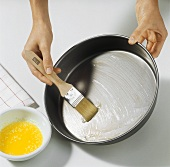 Greasing baking tin with brush and melted butter