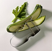 Slicing courgettes thinly lengthways using potato peeler