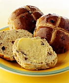 Buttered hot cross buns on plate