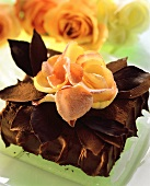 Chocolate gateau with chocolate leaves and rose petals