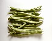 Several green runner beans against white background