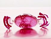 Ein rosa Bonbon in Papier gewickelt