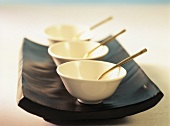 White Asian bowl on black serving platter