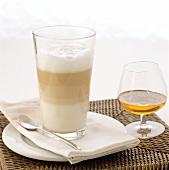 A glass of latte macchiato and a glass of cognac