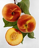 Half a peach and two whole peaches with leaves