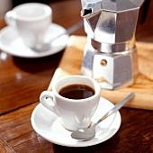 A cup of espresso in front of Italian espresso pot
