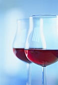 Two glasses of red wine against blue backdrop