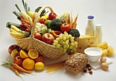 Various foodstuffs in and beside a basket